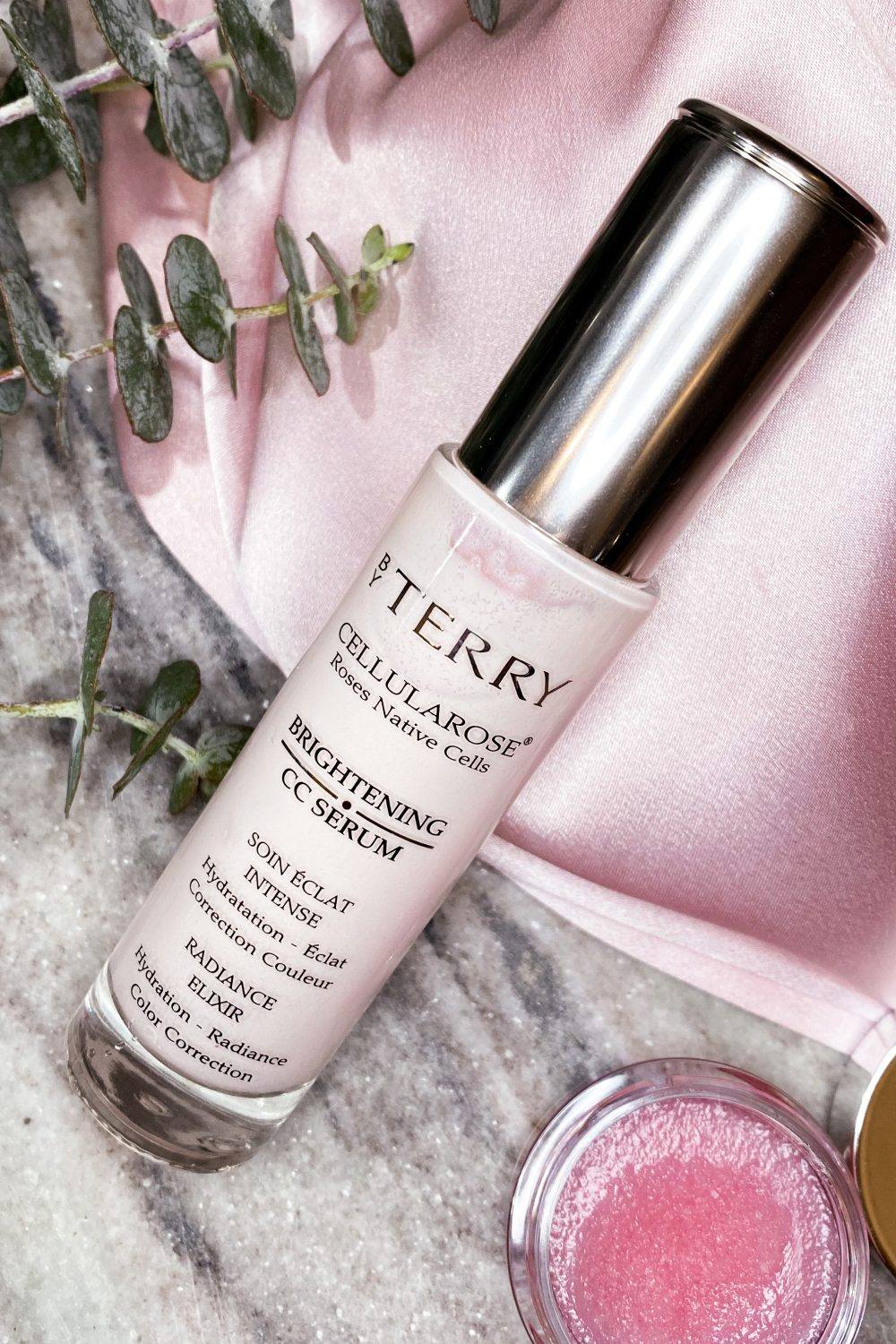 By Terry Rose Colored CC Serum laying with eucalyptus on pink silk and grey marble