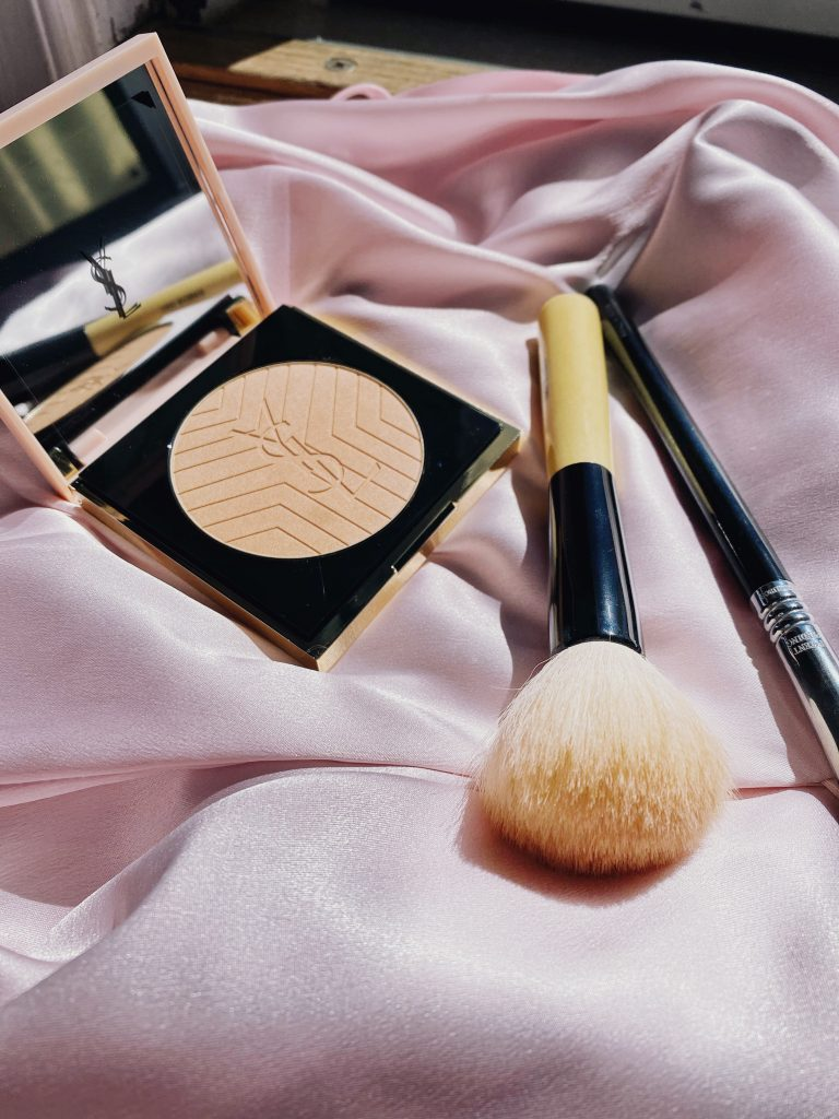 YSL Face powder with a fluffy face makeup brush on a pink silk backdrop
