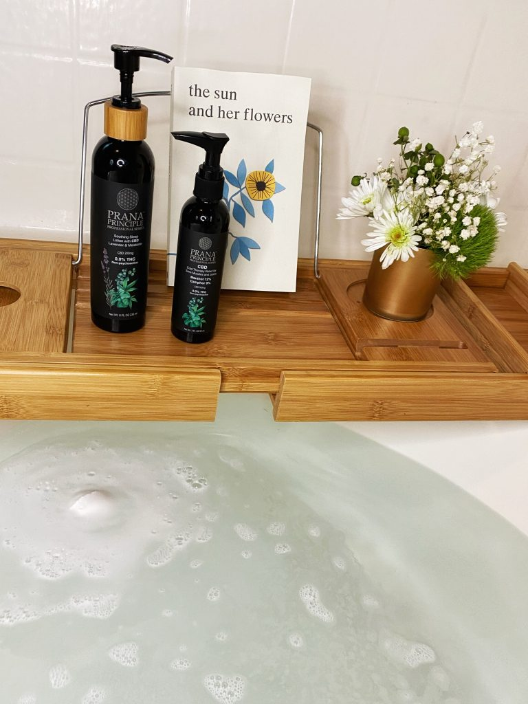 Calming bath with a CBD bomb, a book, flowers, and CBD lotions